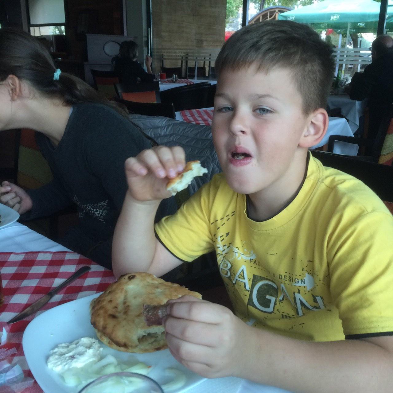 Enej in porcija čevapov v lepinji z kajmakom